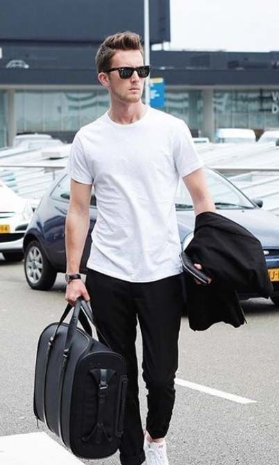 black pants, a white tee, white sneakers and a black bag to travel with style
