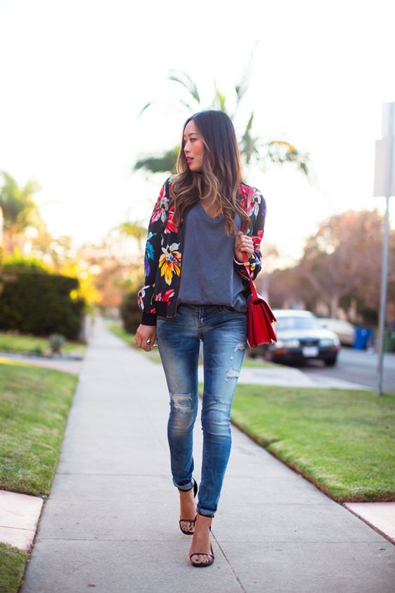 ripped jeans, black heels, an oversized grey tee, a black floral print jacket and a red bag