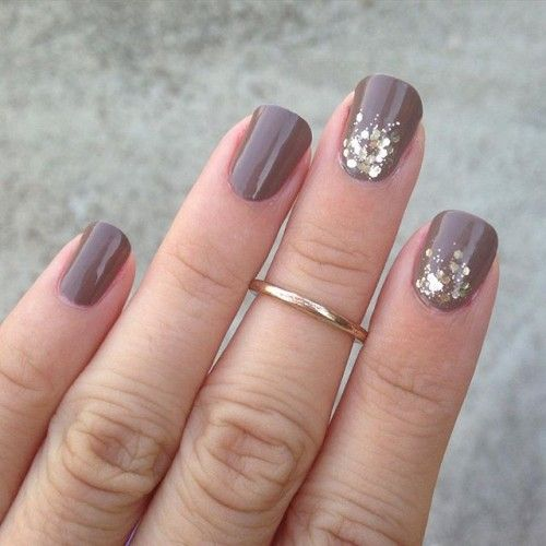 rounded taupe nails with gold glitter touches