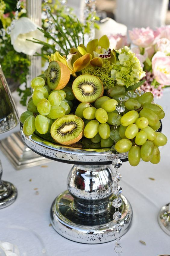a tropical centerpiece with green grapes, kiwi, moss and orchids on a silver stand