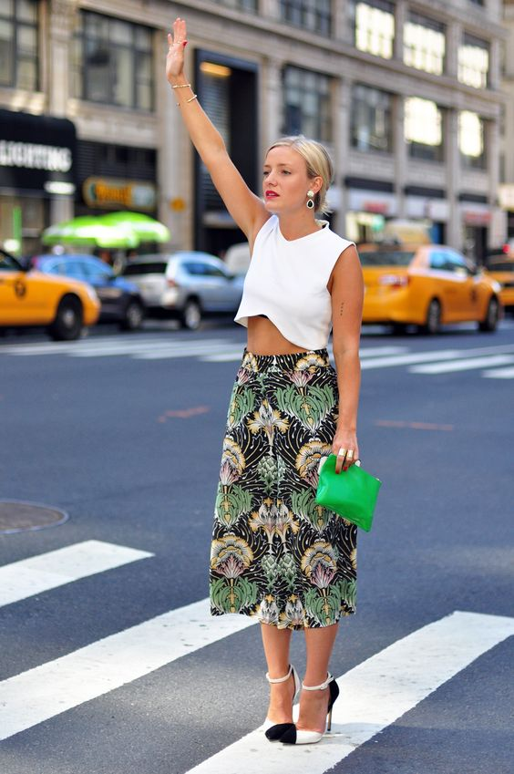 a white crop top, a printed tropical-inspired midi skirt, black and white heels and a green bag