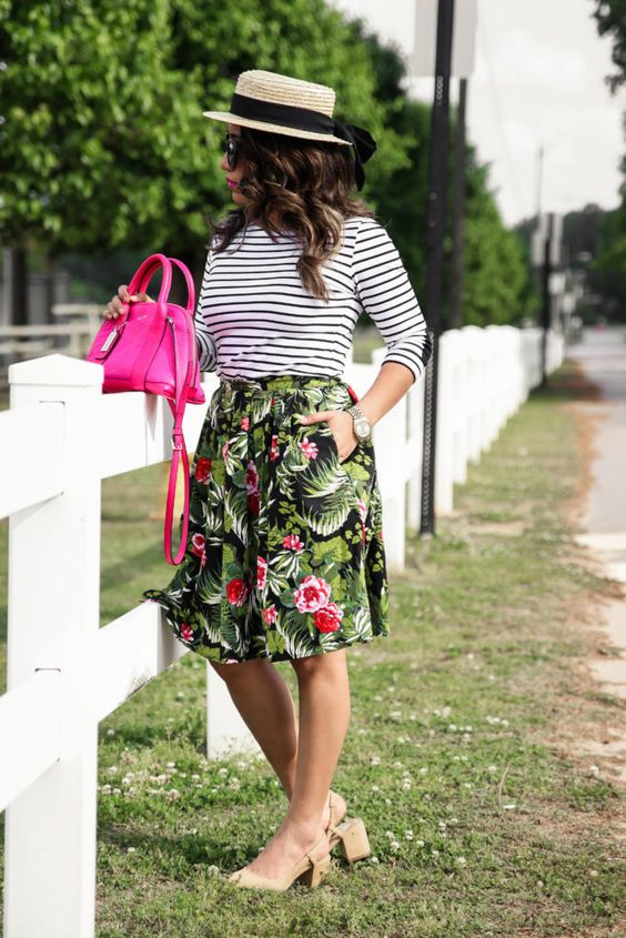 a tropical print knee skirt, a striped black and white long sleeve, neutral heels and a hot pink bag