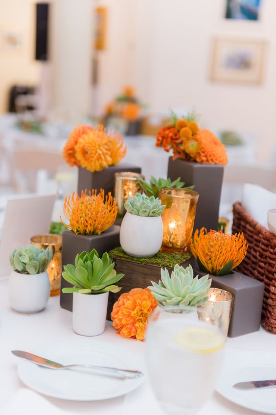 a modern wedding centerpiece with succulents and orange blooms