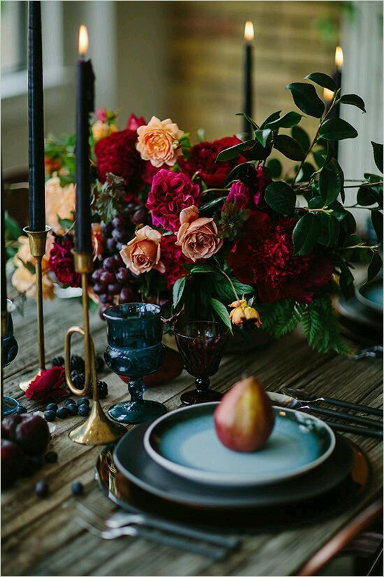 a colorful centerpiece with red, orange flowers, ferns and grapes for a moody fall wedding