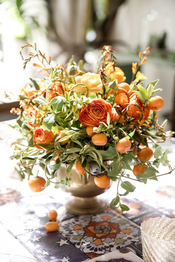 a bronze vase with orange ranunculus and kumquats for a summer wedding