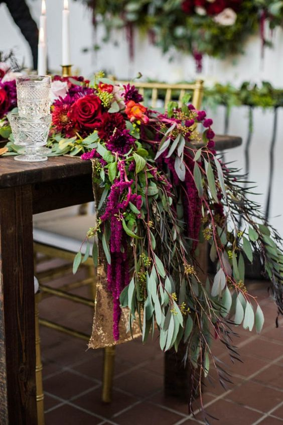 lush fuchsia and red blooms and lots of greenery for a stunning table runner