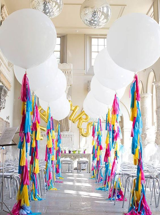 oversized white balloons with colorful fringe for decorating a wedding aisle