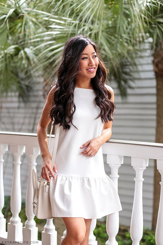 a white mini dress with a ruffled edge and no sleeves, a white bag