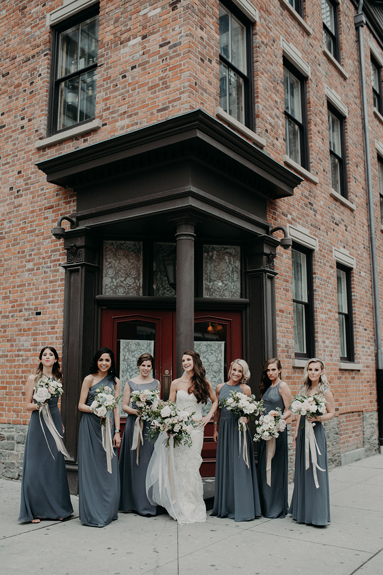 bridesmaids wearing dove grey gowns - photo by Scarlet ONeill http://ruffledblog.com/industrial-space-meets-enchanted-forest-wedding