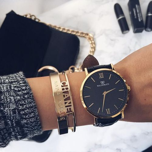 a large black and gold watch and gold bracelets to highlight it