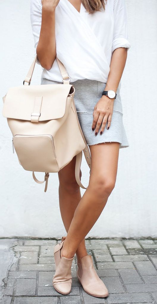 a white twist top, a grey skirt from H&M, nude boots and a large creamy backpack