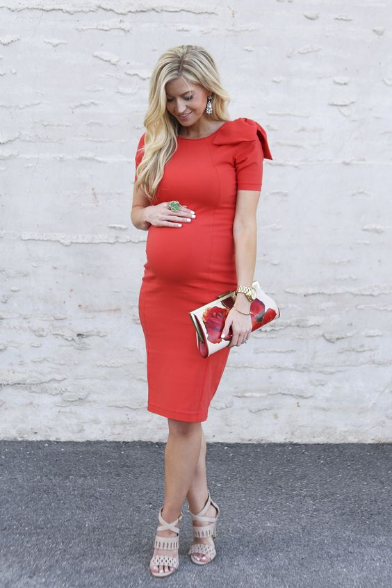 a red knee dress with a bow on the shoulder, nude heels and a floral clutch
