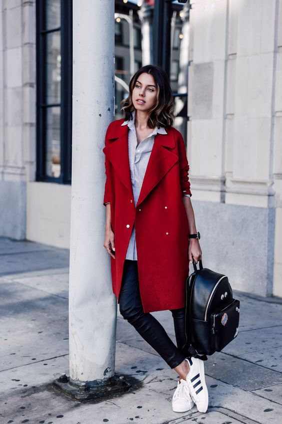 black leather pants, a thin striped shirt, a red coat and white sneakers, a black backpack
