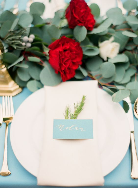 a lush foliage and red bloom table runner and gold cutlery for a cool tablescape