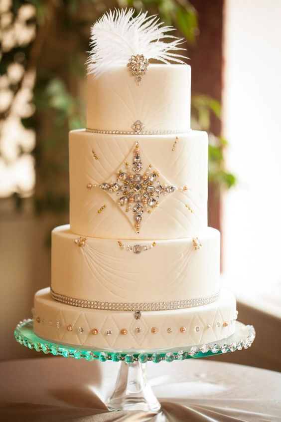 a gorgeous white wedding cake with beads, rhinestones and a feather on top