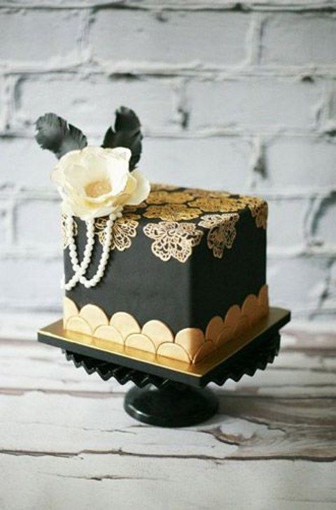 a mini square cake in black and gold, with scallops, lace flowers, pearls, a sugar flower and black feathers