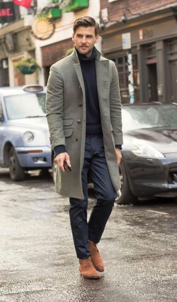 a black sweater, pants, amber boots and an olive green coat