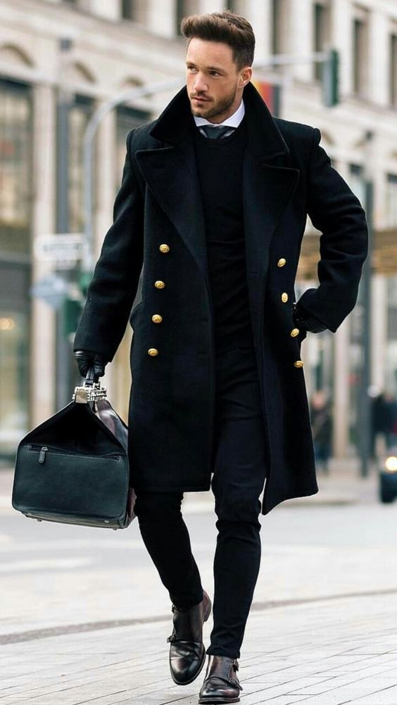 a total black look with jeans, boots and a double breasted coat