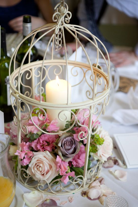 a white birdcage with lush pink blooms and a candle but be careful not to burn the flowers