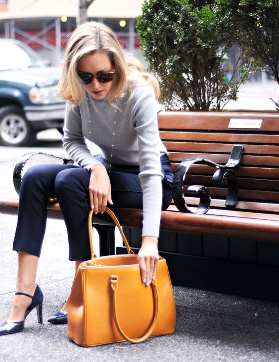cropped navy pants, a grey long sleeve top, navy shoes, a pearl necklace and a mustard yellow bag