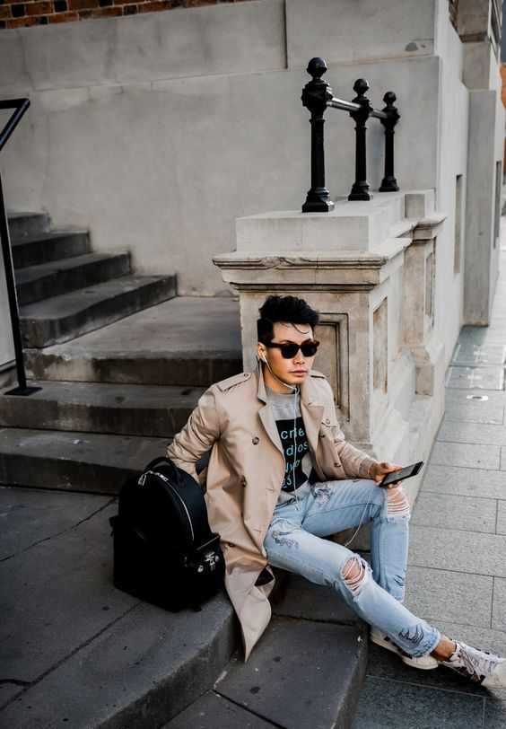 a casual fall look with a beige trench, ripped jeans, sneakers and a grey t-shirt