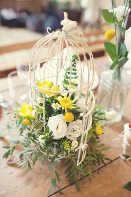 a birdcage with white and yellow blooms and foliage is cute and simple to make