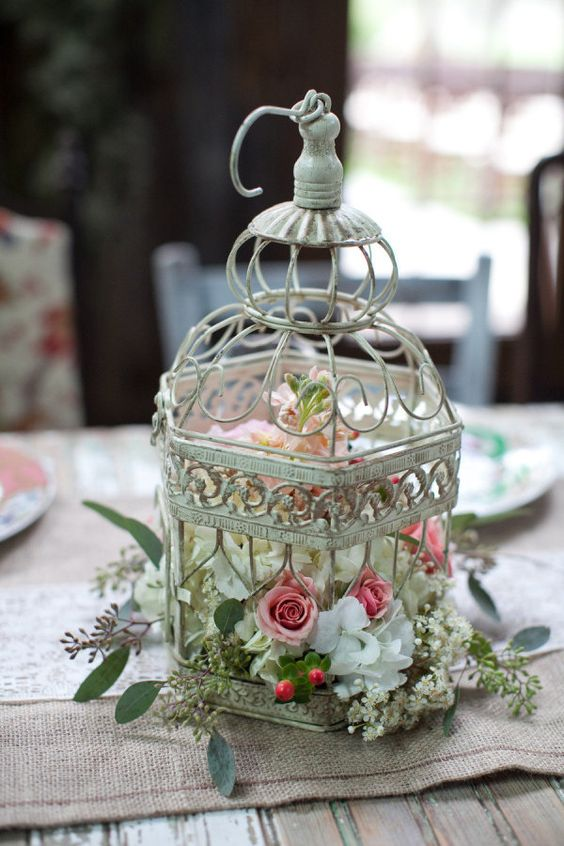 a shabby chic bird cage with white, pink and blush florals
