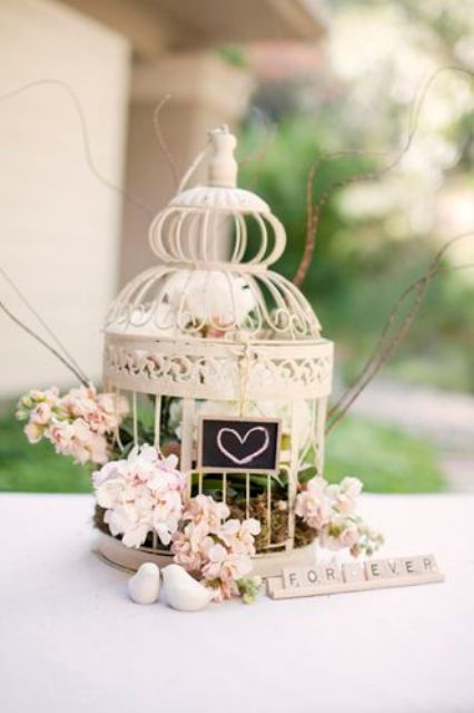 a small cage with a chalkboard sign, pink blooms and greenery