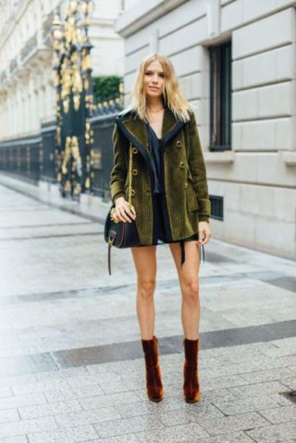 an olive green short coat with large buttons, a black crossbody and burnt orange velvet boots
