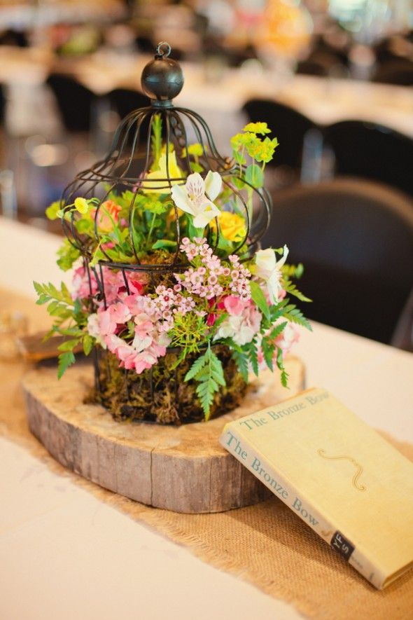 a rustic vintage cage on a wooden slice with moss, foliage and pink blooms for a woodland wedding