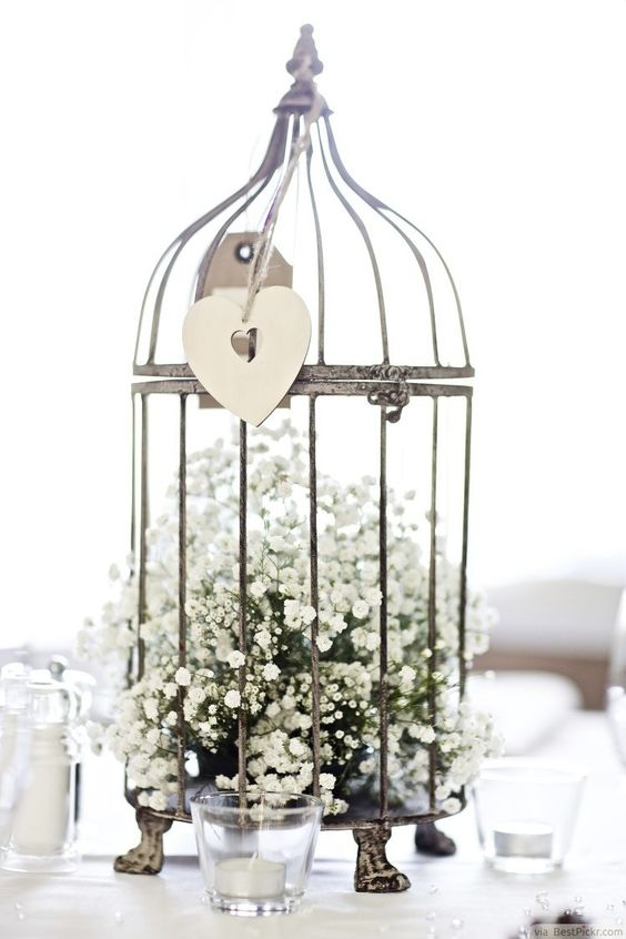 a metal cage on legs with baby's breath inside and a cutout heart hanging outside