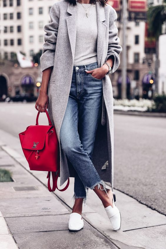 a grey top, a grey midi coat, cropped blue jeans, white slipons and a red backpack