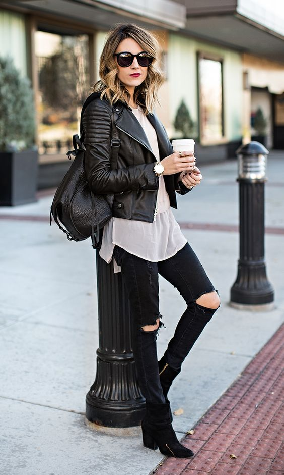 black distressed jeans, black suede booties, a white shirt, a black moto jacket and a backpack