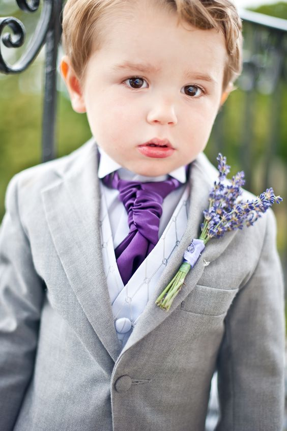 a grey suit with a neutral waistcoat and a purple tie