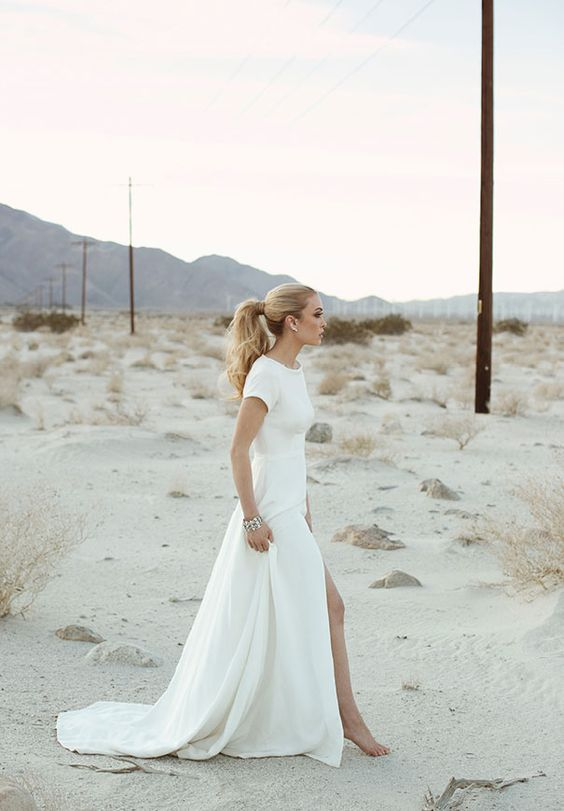 minimalist short sleeve wedding dress with a front slit and a high neckline