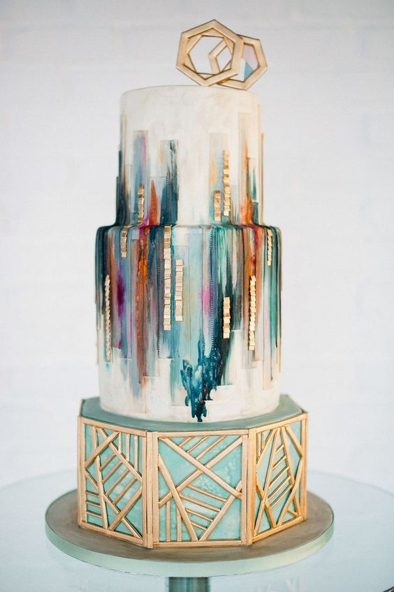 a wedding cake with colorful green, teal, orange, purple strokes, geometric gold decor and toppers