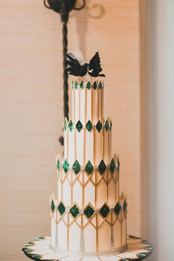 a unique wedding cake with spiky emeralds, gold geo prints and black bird toppers