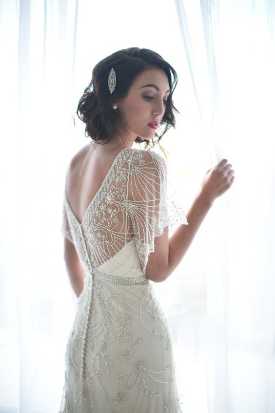 an embroidered and beaded wedding dress with a V cut on the back, a row of buttons and flowy sleeves