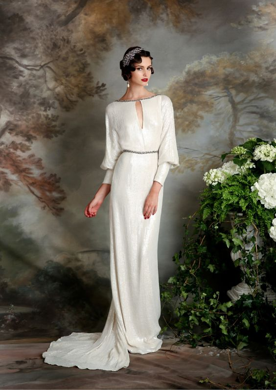 an ivory wedding dress with long sleeves, a loop cutout and beading on the neckline and waist