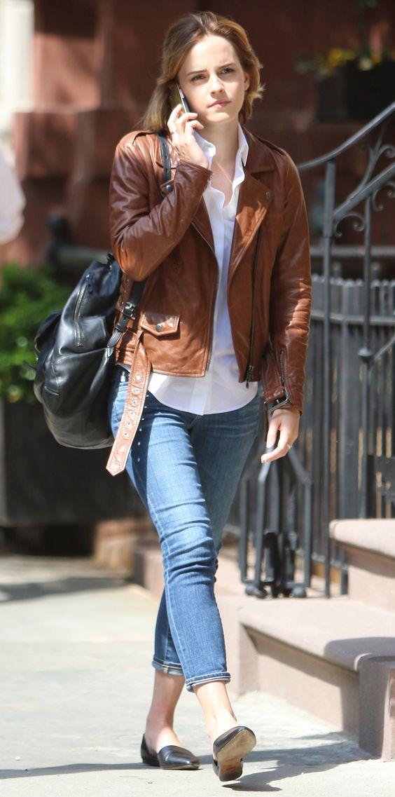 black flats, cropped blue jeans, a white shirt, a brown leather jacket and a black backpack