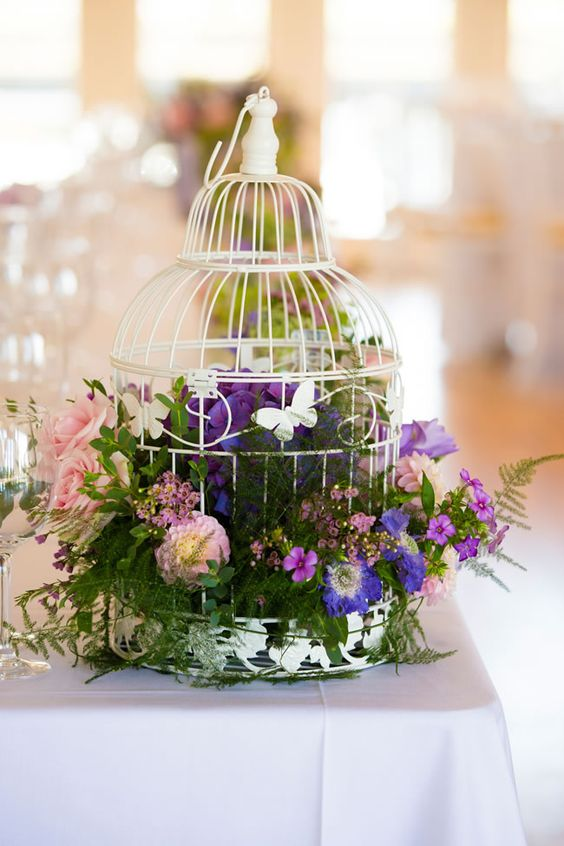 a white birdcage with lush foliage, purple and pink blooms for a colorful big day