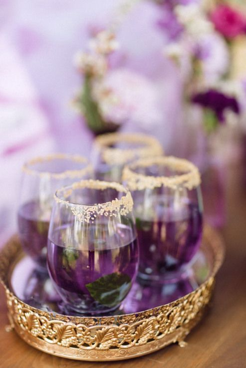 purple signature cocktails with mint and a gold rim