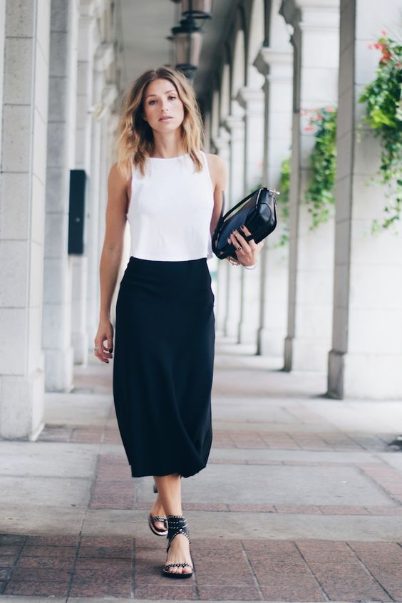 a black midi skirt, a white sleeveless crop top, black spiked shoes and a black bag