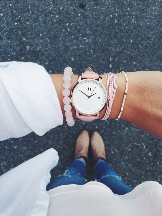 a watch with a pink leather band and pink bracelets for a feminine look