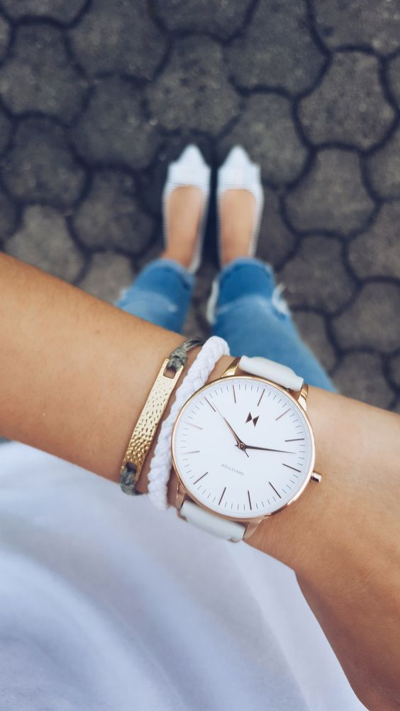 a large watch on a white leather band with a couple of matching bracelets accentuates your look