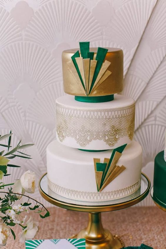 an art deco wedding cake with metallic gold decor and layers, gold lace and emerald touches