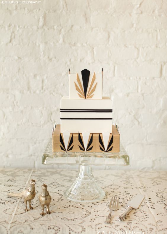 a square wedding cake with black and gold geometric decor