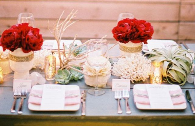 a wedding tablescape with white and gold glitter vases and red roses