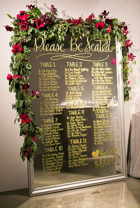 an oversized mirror seating chart with gold calligraphy, red roses and greenery
