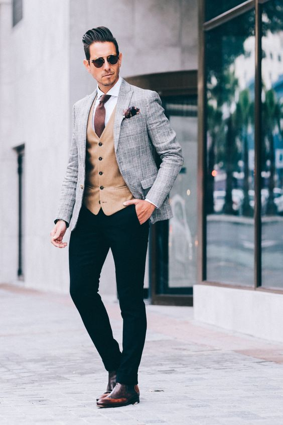 black pants, am amber vest, a white shirt, a brown tie and a grey jacket highlighted with cognac shoes